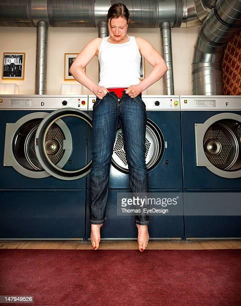 Femme essayant d'entrer dans une paire de Jeans Skinny