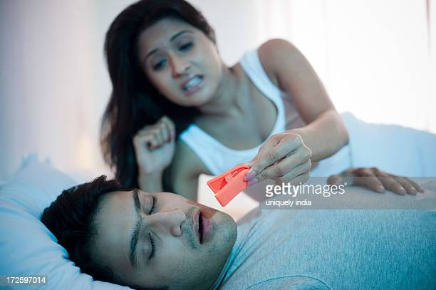 Woman trying to fix clothespin on her snoring husbands nose on bed