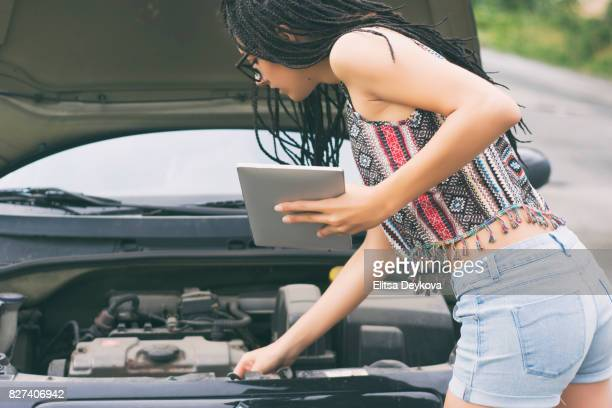 Woman trying to fix her car