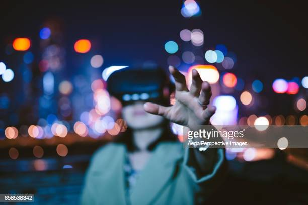 Woman trying virtual reality simulator headset in Urban city at Night