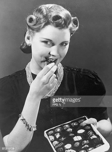 A woman tucks into a box of chocolates circa 1940