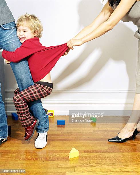 Woman tugging girl (2-4) clinging to mother's leg, low section