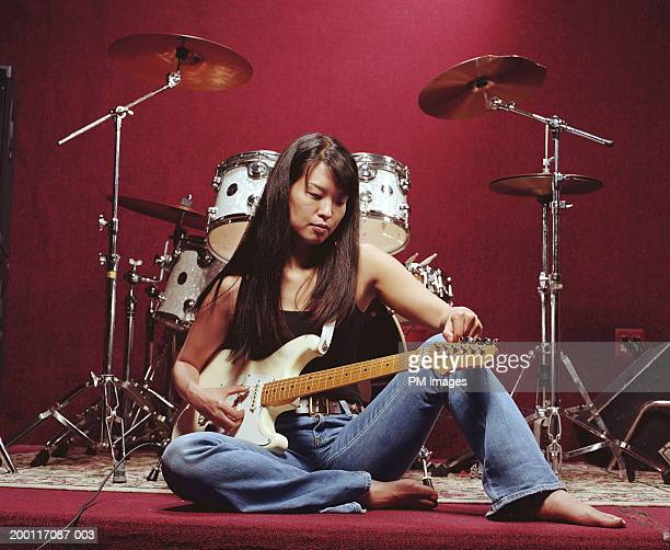 Woman tuning guitar infront of drums
