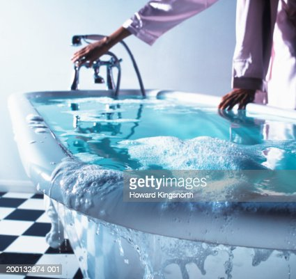 Woman turning bath tap, water overflowing (focus on edge of bath)