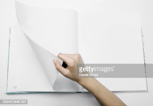 Woman turning numbered blank page in photograph album, close-up