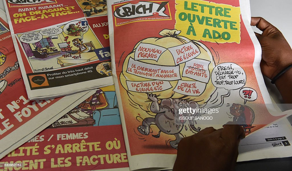 A woman turns the pages of a satirical newspaper made of cartoons in Abidjan on May 24, 2016. Press cartoonist took part in an exhibition at the French Institute gathering 20 years of cartoons in the media on the history of Ivory Coast, until the post-electoral crisis of 2010-2011 that killed 3,000 people. / AFP / ISSOUF