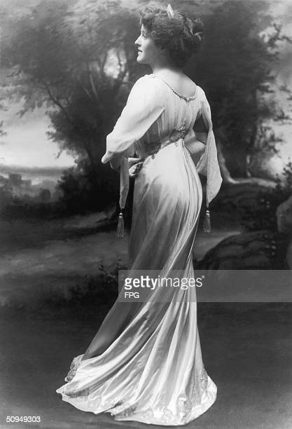 A woman turns to show off the elegant folds of her tasseled floorlength gown circa 1910