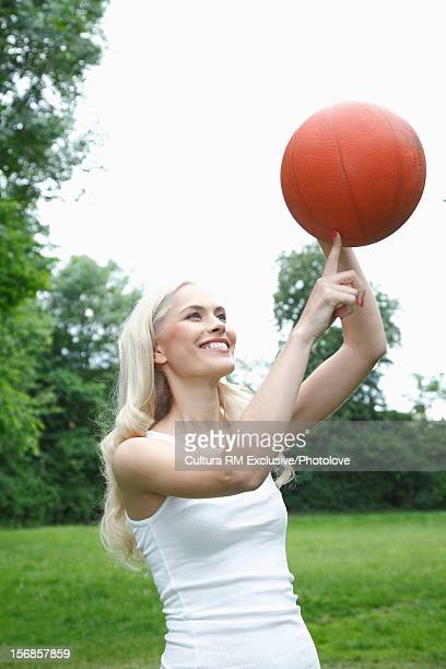 Woman twirling basketball in park