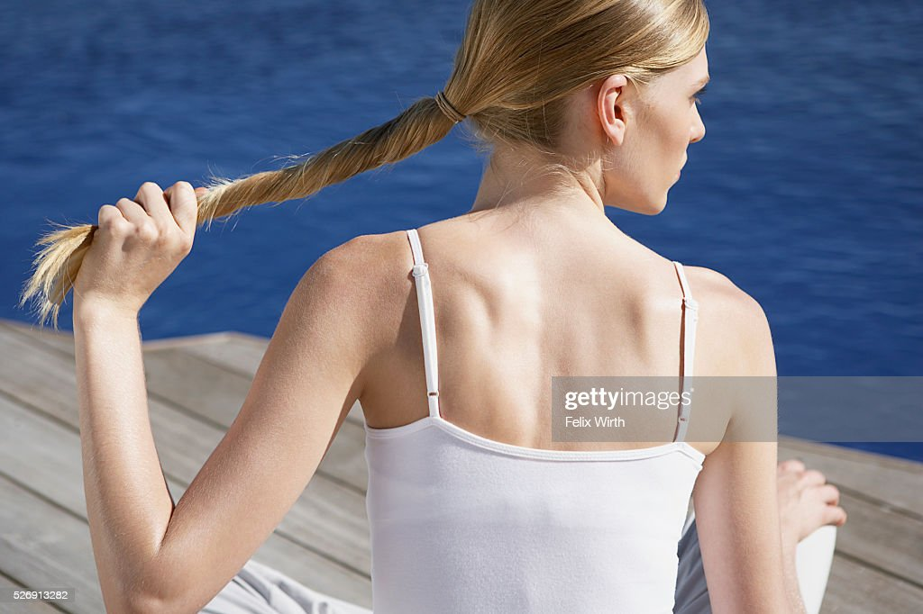 Woman twisting hair : Stock Photo
