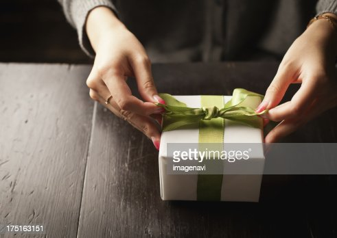 Woman tying a gift box with a ribbon getty images woman tying a gift box with a ribbon negle Images