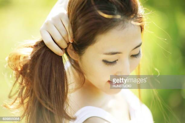 woman tying her hair in the park