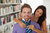 Woman tying husband's necktie for him