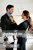 Woman tying husband's tie in kitchen