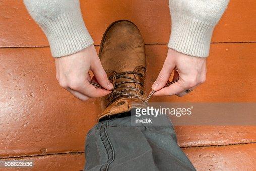 Woman tying male shoelaces : Stock Photo