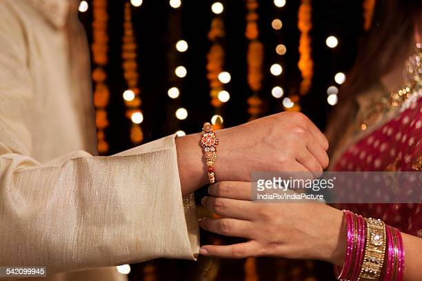 Woman tying rakhi on her brothers hand