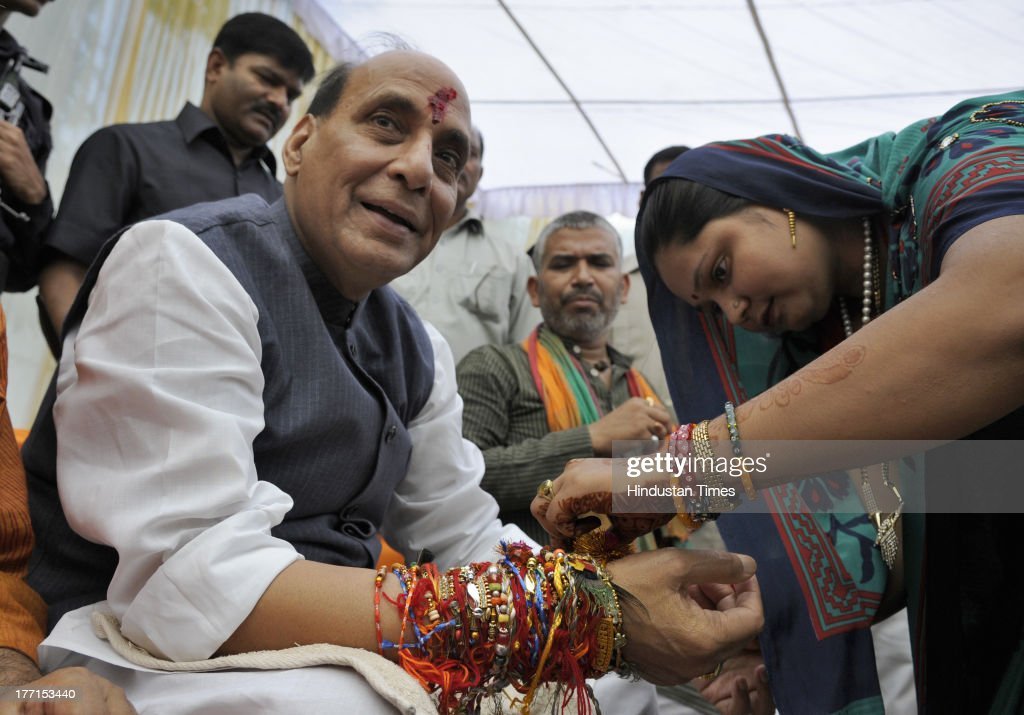 A woman tying Rakhi on the wrist of BJP President Rajnath Singh on the occasion of Rakhi festival at his house on August 21, 2013 in New Delhi, India. Raksha Bandhan, the festival of love between brothers and sisters, is being celebrated across the country today with full enthusiasm.