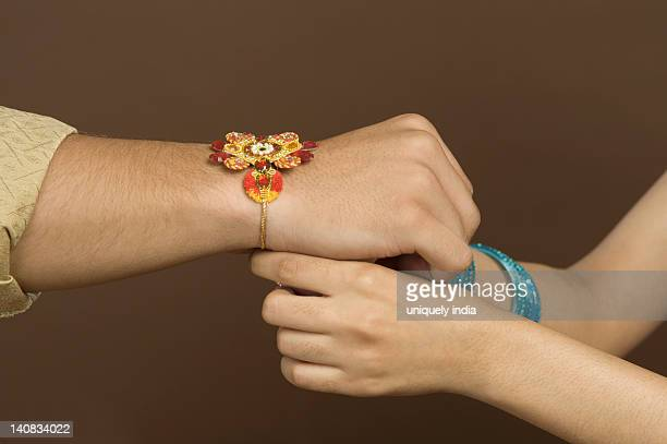 Woman tying rakhi on the wrist of her brother