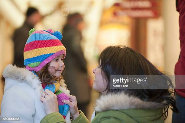 Woman tying scarf of her daughter while shopping in winter