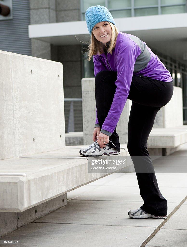 Woman tying shoe before exercising. : Stock Photo