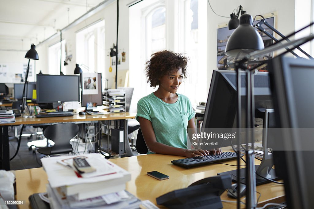 Woman typing on computer at her desk : Stock Photo