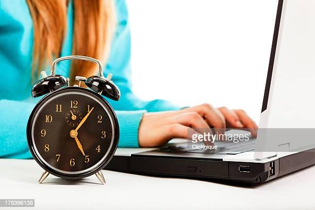 Frau Eingabe am laptop mit Uhr zeigt fünf in der Nähe