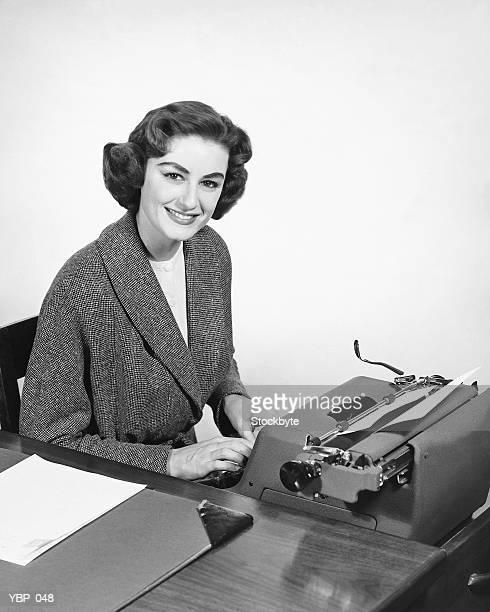 Mujer escribiendo, y sonriente posando