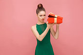 Woman unboxing red gift box looking inside, ahve sadness look. Expression emotion and feelings concept. Studio shot, isolated on pink background