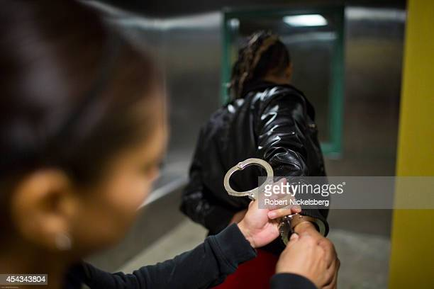 A woman under arrest has her handcuffs removed in a holding cell February 1 2013 by vice squad officer with the Los Angeles Police Department's South...