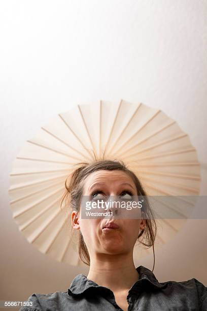 Woman under ceiling lamp as hat
