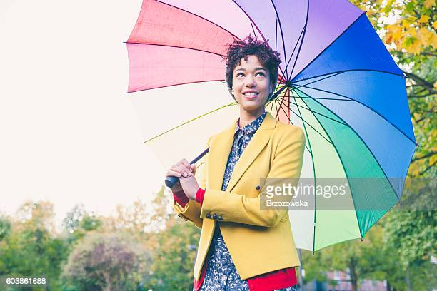 Woman under colorful umbrella in a park (London, UK)