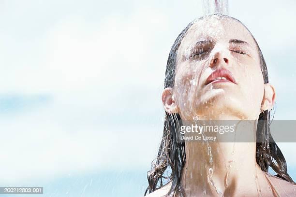 Woman under shower, outdoors