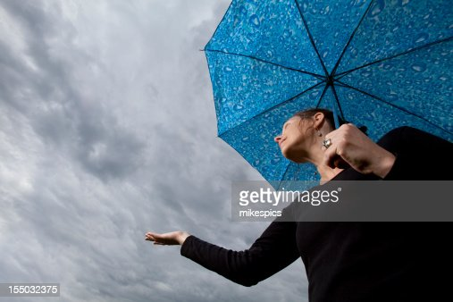 Woman under umbrella holding hand out to check for rain : Stock Photo