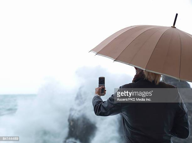 Woman under umbrella photographs waves with cell