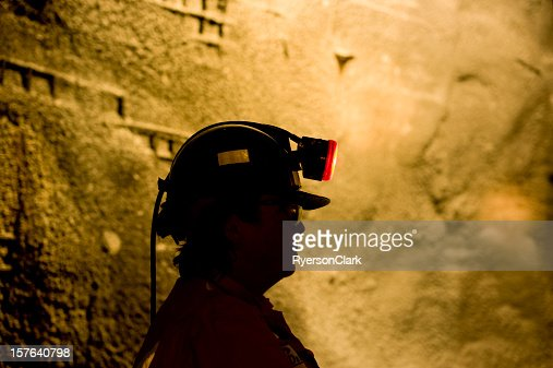 Woman Underground Mine Worker with Lamp On.
