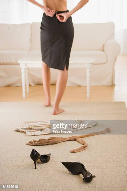 Woman undressing next to clothing on floor