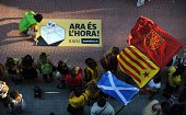 A woman unfolds a banner reading 'Now it's time' as a protester waves flags from Navarra Catalonia and Scotland during a demonstration in support of...