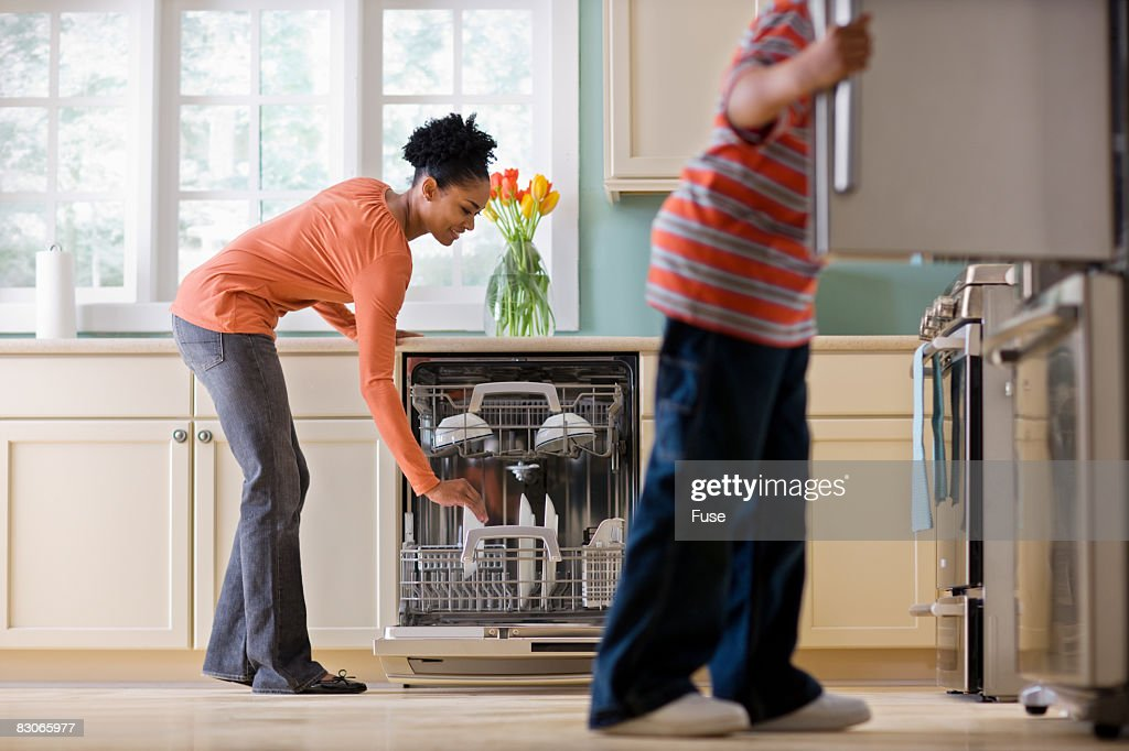 Woman Unloading Dishwasher While Son Looks in Refrigerator