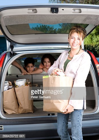 Woman unloading groceries from car, children in car