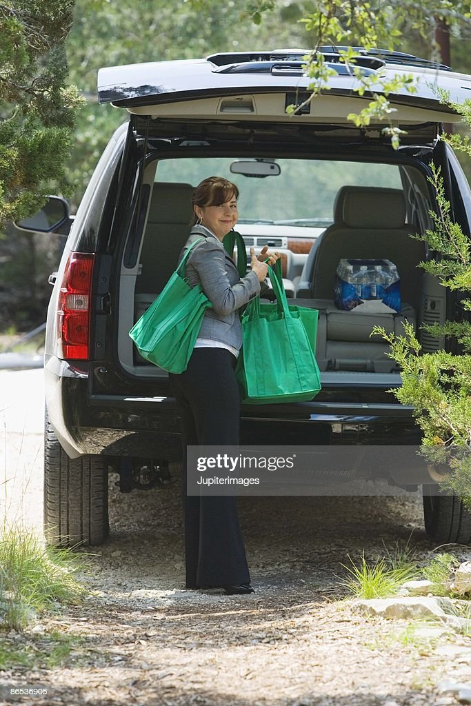 Woman unloading groceries from hatchback