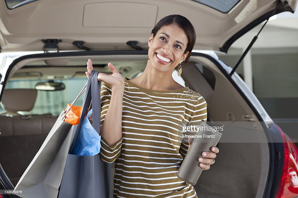 Woman unloading shopping from car : Stock Photo