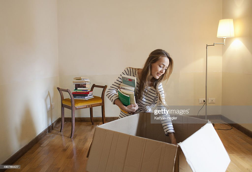 woman unpacking box with books in her new house : Stock Photo