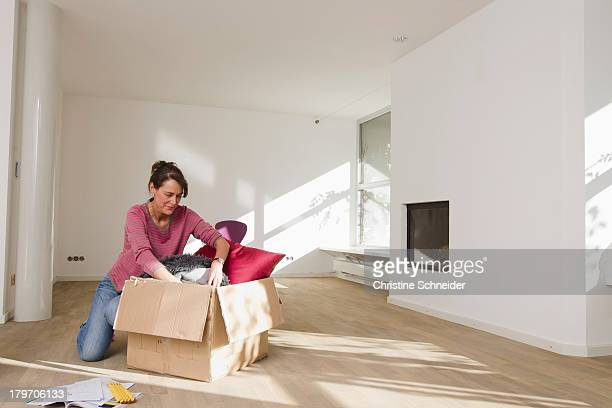 Woman unpacking cardboard box in empty room