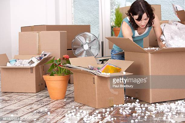 Woman unpacking cardboard boxes