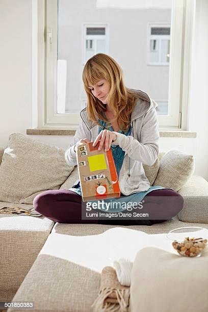 Woman Unpacking Parcel On Sofa