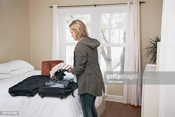 Woman unpacks suitcase