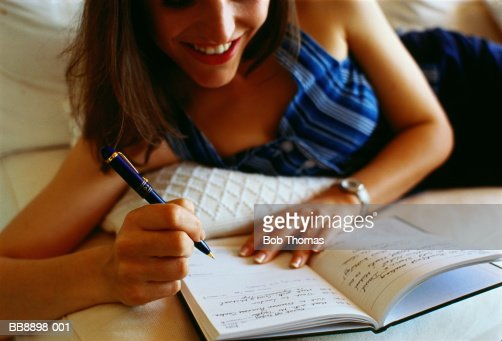 Woman updating diary, lying on bed : Stock Photo