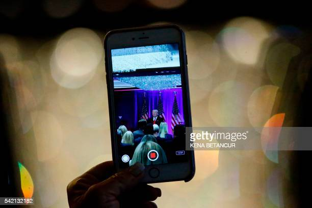 A woman use her phone to do a video while presumptive Republican presidential nominee Donald Trump speaks at the Trump Soho Hotel in New York on June...