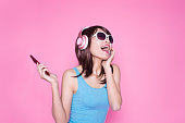 woman use phone listen music on the pink background