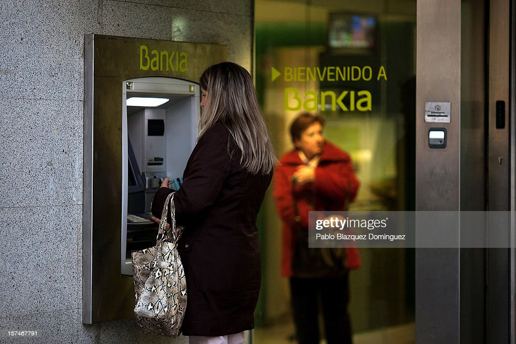 A woman uses a Bankia's cash point at Plaza de Castilla on December 3, 2012 in Madrid, Spain. Spain has formally requested 39.5 euro billions bank bail-out of European funds. Economy Ministry of Spain, Luis de Guindos said that 37 euro billions will be paid for the four nationalized banks Bankia, Catalunya Banc, NCG Banco and Banco de Valencia while 2.5 euro billions will be for the 'bad banks'.