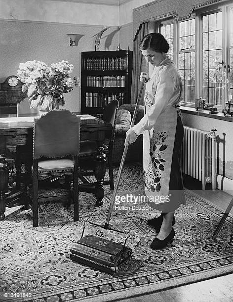A Woman Uses Carpet Sweeper To Clean Her Dining Room Rug News Photo